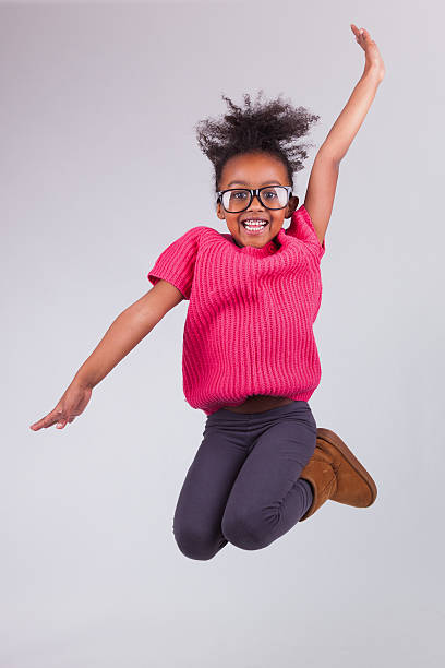 a portrait of a young girl jumping up and making a pose - african youth jumping for joy stock photos and pictures
