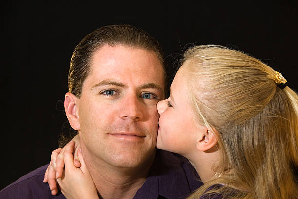 Portrait of a young girl kissing her father  little girl kissing dad on cheek stock pictures, royalty-free photos & images