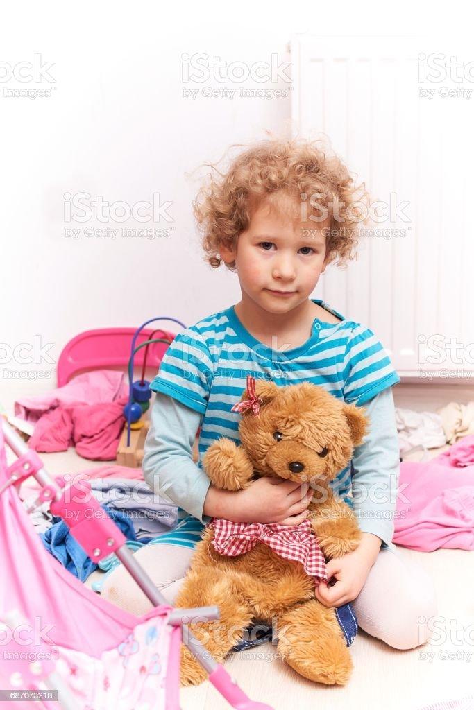 Porträt eines jungen Mädchens posiert mit einem Teddy-Bären unter das Chaos im Zimmer Lizenzfreies stock-foto