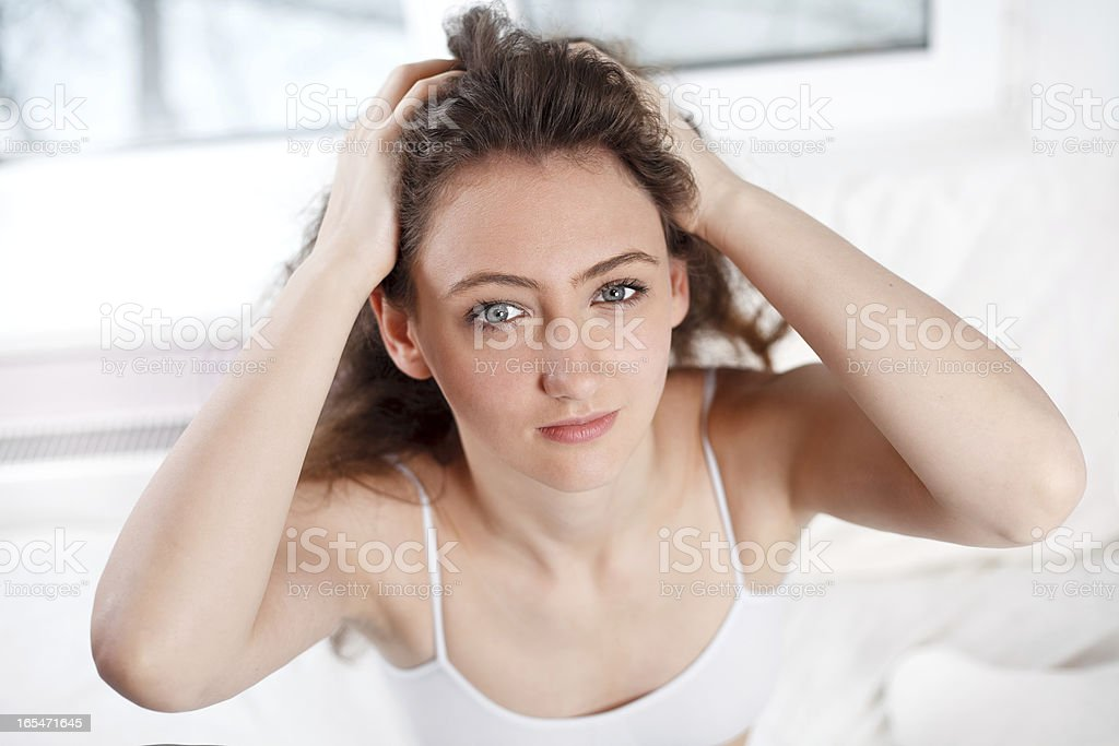Portrait of a young girl recovering her hairs with hands royalty-free stock photo