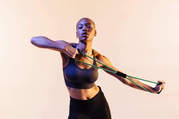 portrait of a young girl stretching a resistance band - carlos david stock pictures, royalty-free photos & images