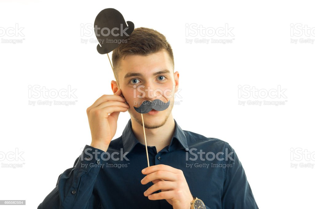 Portrait of a young guy who stands in the Studio and keeps the paper Dummies for photo near face stock photo