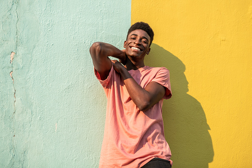 Portrait of a young handsome African man looking at the camera . He is leaning on light blue/yellow wall.