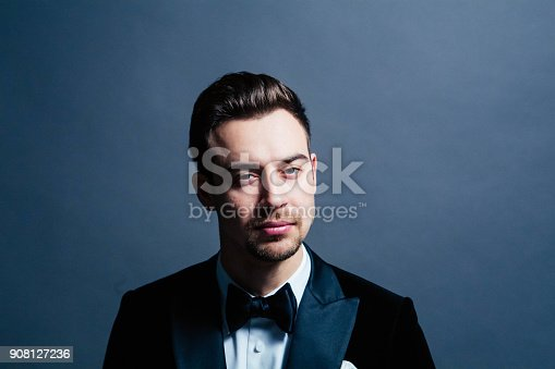istock Portrait of a young handsome man in a suit, seriously looking at the camera 908127236
