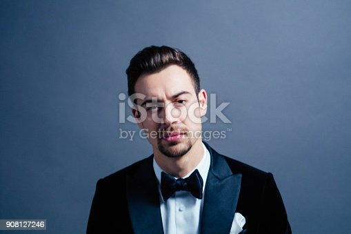 istock Portrait of a young handsome man in a suit, seriously looking at the camera 908127246