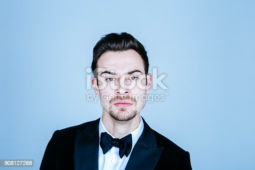 istock Portrait of a young handsome man in a suit, seriously looking at the camera 908127268