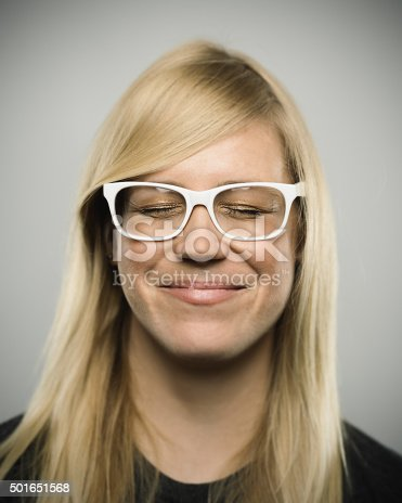 Studio portrait of an australian young adult woman looking at camera with happy expression. The woman has around 25 years and has long blond hair and white glasses. Vertical color image from a medium format digital camera. Sharp focus on eyes.