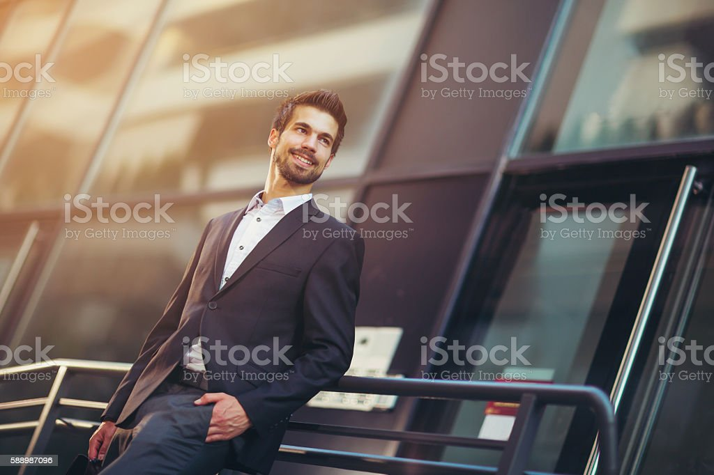 Portrait of a young happy businessman outside the office building stock photo