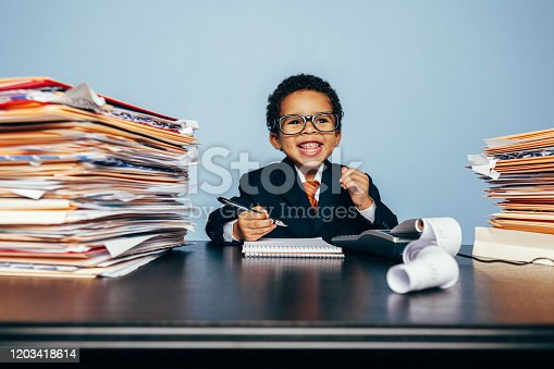 A young boy dressed in business suit and necktie, is sitting at his office desk playing tax accountant and financial advisor. On his desk sits many financial documents and a calculator. This boy is ready for crunch your numbers and make the most of your money.