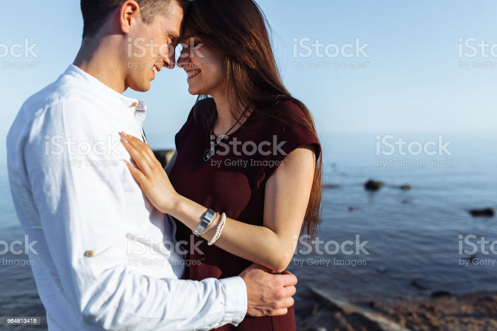 portrait of a young, happy, loving couple standing on stones at sea, in the arms, and looking at each other, advertising and inserting text royalty-free stock photo