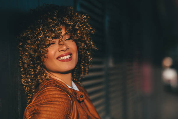 portrait of a young happy woman in a brown leather jacket with blond afro curly hair on the street - capelli ricci foto e immagini stock