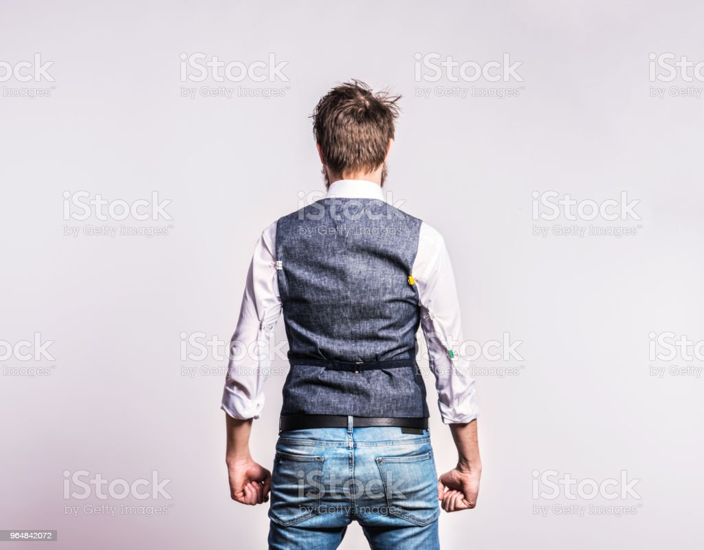 Portrait of a young hipster man in a studio. Copy space. royalty-free stock photo