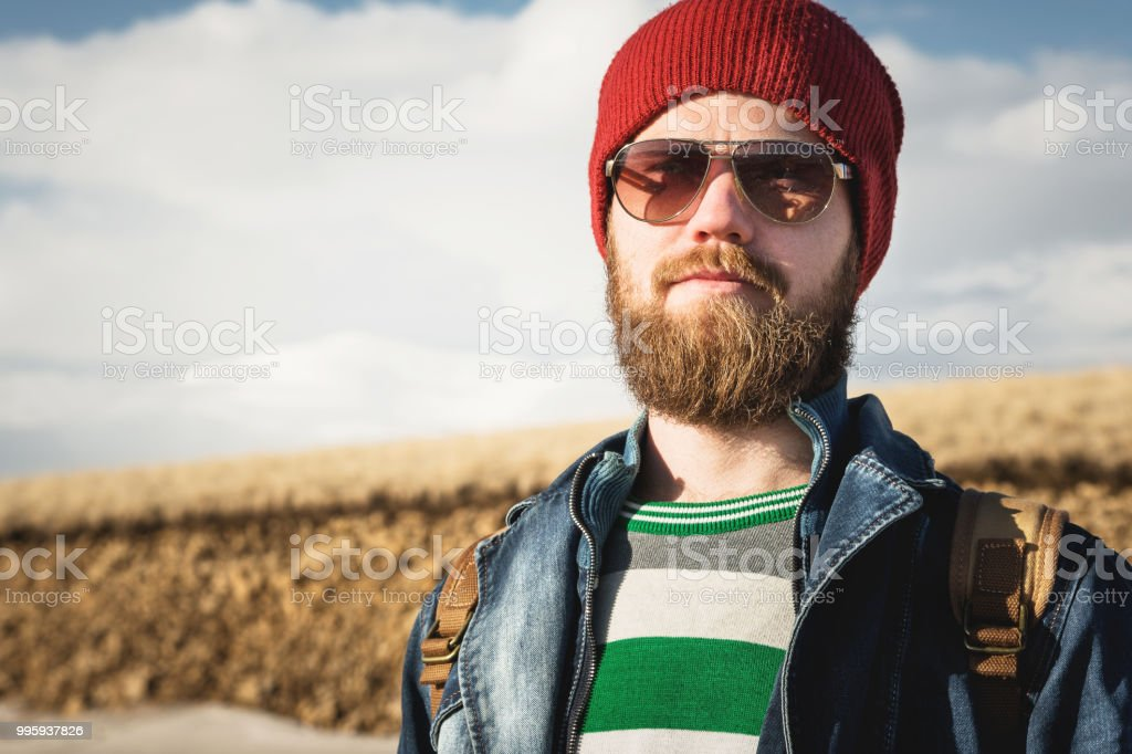 Portrait of a young hipster man wearing sunglasses and a hat. A smiling bearded  man wearing sunglasses. Happy man with a beard - Stock image . 24428ebb0b78