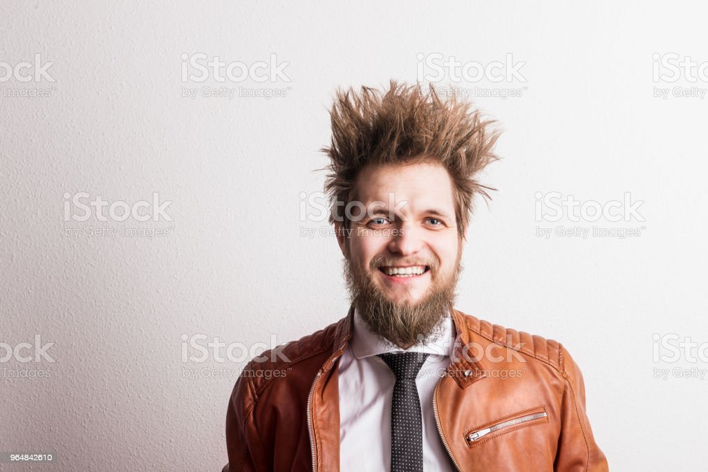 Portrait of a young hipster man with messy hairstyle in a studio. Copy space. royalty-free stock photo