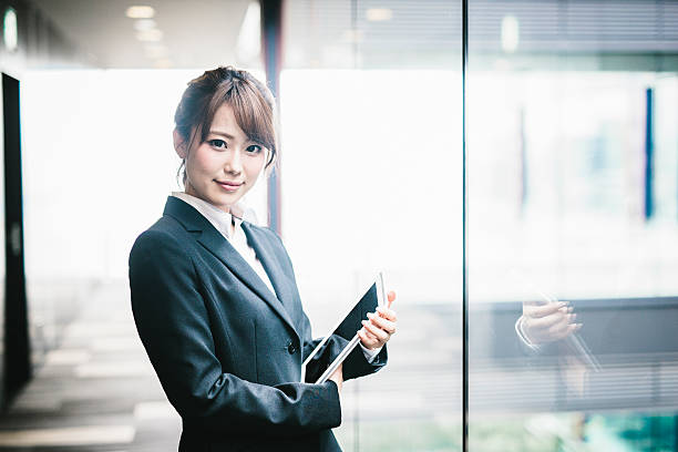 Portrait of a Young Japanese Business Woman A portrait of a young Japanese business woman. She is standing in the hallway, next to a window which is a vantage point over the nearby park. She has her tablet with her, which allows her to always stay in though with what is going on in her business. She has serious attitude yet her look is calm. Looking here, she has a small smile on her face. only japanese stock pictures, royalty-free photos & images