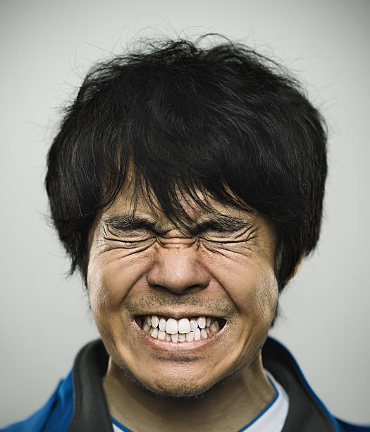 Portrait of a young japanese man under stress Studio portrait of a japanese young man with closed eyes and clenched teeth. The man has around 30 years and has long black hair and casual clothes. Vertical color image from a medium format digital camera. Sharp focus on eyes. clenching teeth stock pictures, royalty-free photos & images