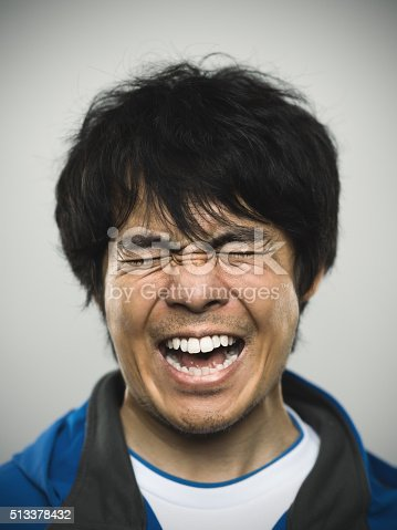 Studio portrait of a japanese young man with closed eyes and clenched teeth. The man is around 30 years and has long black hair and casual clothes. Vertical color image from a medium format digital camera. Sharp focus on eyes.