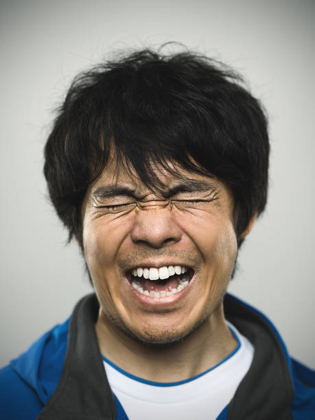 Portrait of a young japanese man under stress Studio portrait of a japanese young man with closed eyes and clenched teeth. The man is around 30 years and has long black hair and casual clothes. Vertical color image from a medium format digital camera. Sharp focus on eyes. clenching teeth stock pictures, royalty-free photos & images