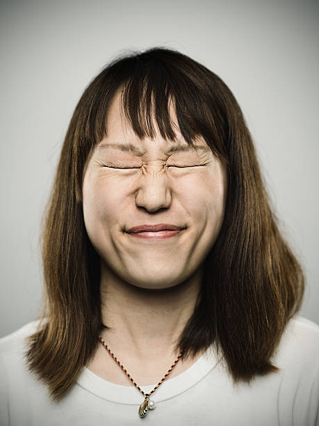 Portrait of a young japanese with closed eyes Studio portrait of a japanese young woman with closed eyes and stressed expression. The woman has around 30 years and has long hair and casual clothes. Vertical color image from a medium format digital camera. Sharp focus on eyes. grimacing stock pictures, royalty-free photos & images