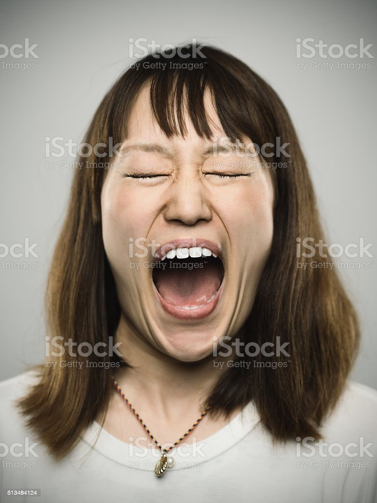 Portrait of a young japanese woman screaming. stock photo