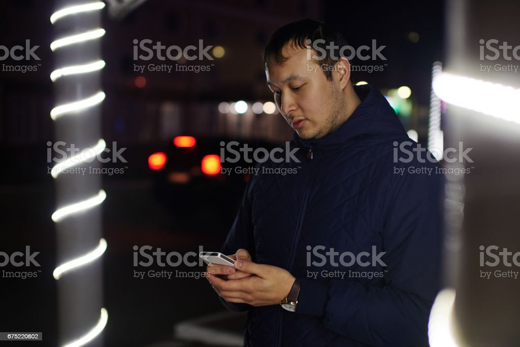 Portrait of a young Kazakh looking at the phone on a night street royalty-free stock photo