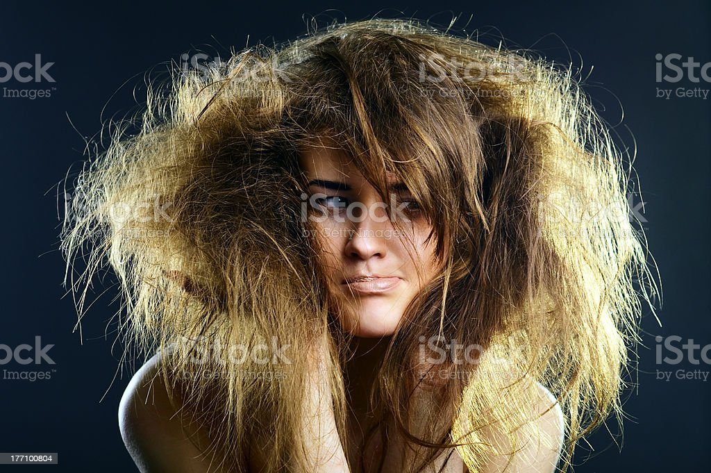 Portrait of a young lady with tousled hair The portrait of a young lady twisting her mouth Adult Stock Photo