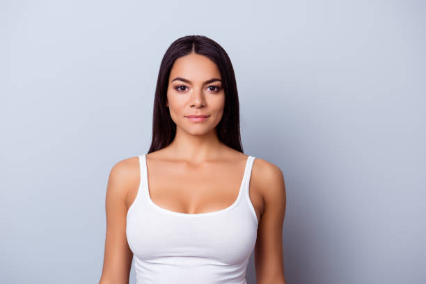 Portrait of a young latino american girl. She is in a casual white singlet standing on the pure light blue background Portrait of a young latino american girl. She is in a casual white singlet standing on the pure light blue background tank top stock pictures, royalty-free photos & images