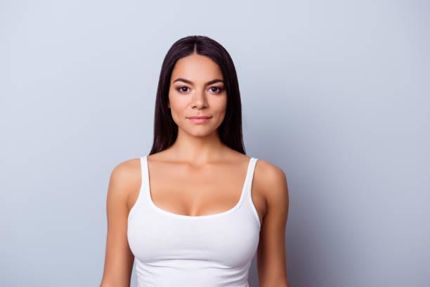 portrait of a young latino american mulatto girl. she is in a casual white singlet standing on the pure light blue background - seno foto e immagini stock