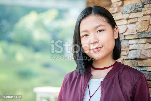 Teenage Girl, Malaysian Ethnicity, Portrait - Close up of a young Malaysian girl looking at the camera while leaning on a tree.
