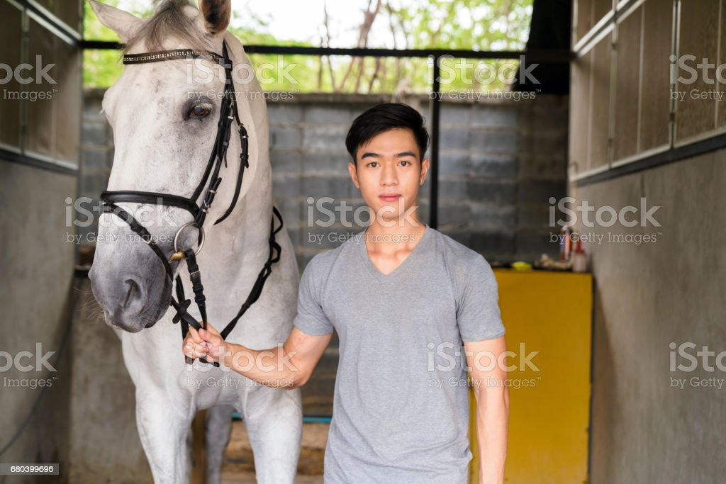 Portrait of a young male horse rider stood with his horse stock photo