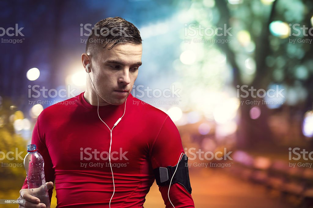 Portrait of a young male jogger at night in a park stock photo