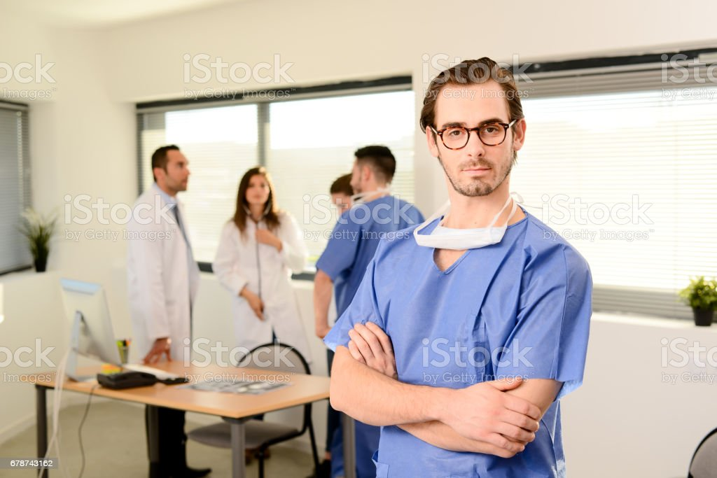 portrait of a young male surgeon residential student in hospital office wearing a operating room outfit photo libre de droits