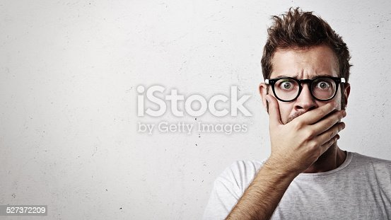 istock Portrait of a young man covering his mouth with hand 527372209