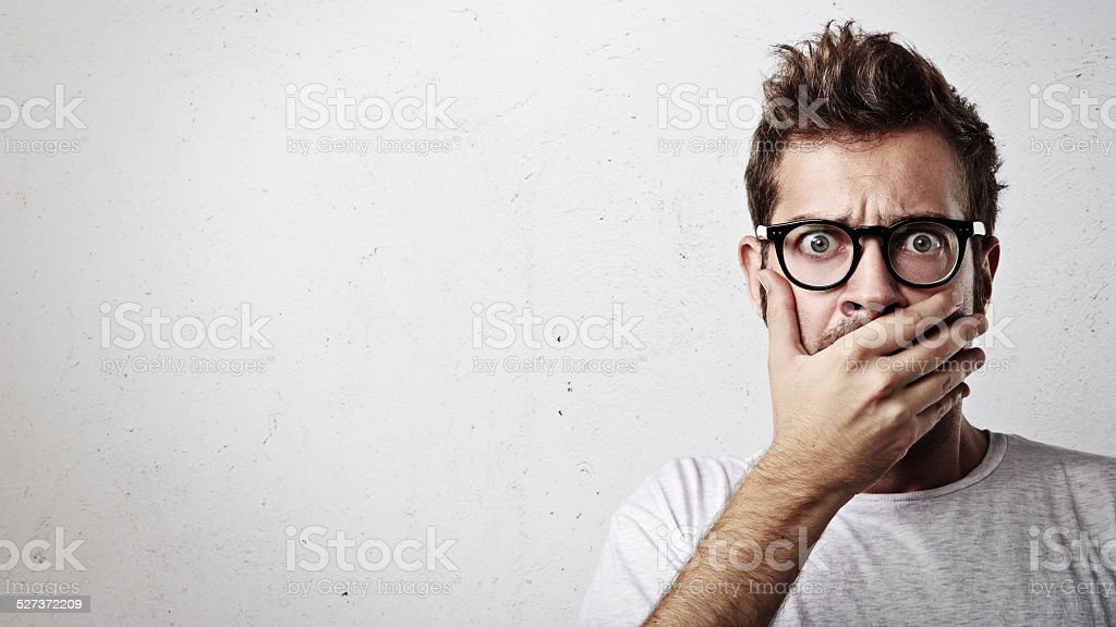 Portrait of a young man covering his mouth with hand stock photo