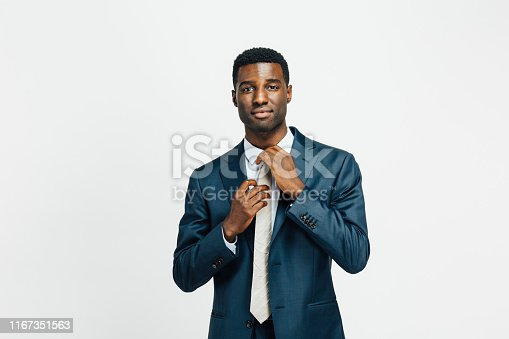 973213156istockphoto Portrait of a young man fixing his tie 1167351563
