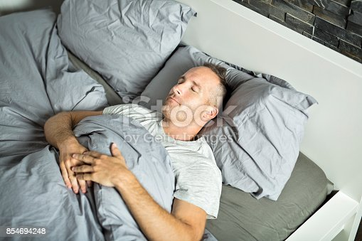 istock Portrait of a young man from above sleeping in  be 854694248