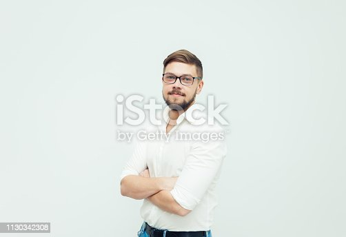 906807208istockphoto Portrait of a young man in glasses dressed in white shirt and casual clothes on a gray background 1130342308