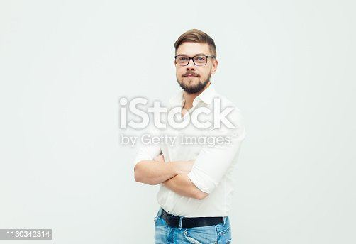 906807208istockphoto Portrait of a young man in glasses dressed in white shirt and casual clothes on a gray background 1130342314