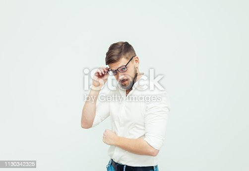 906807208istockphoto Portrait of a young man in glasses dressed in white shirt and casual clothes on a gray background 1130342325