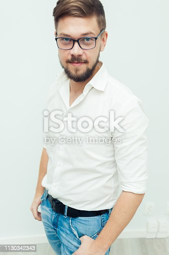 906807208istockphoto Portrait of a young man in glasses dressed in white shirt and casual clothes on a gray background 1130342343