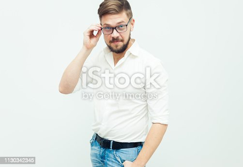 906807208istockphoto Portrait of a young man in glasses dressed in white shirt and casual clothes on a gray background 1130342345