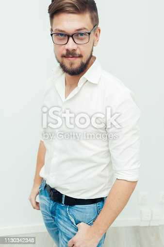 906807208istockphoto Portrait of a young man in glasses dressed in white shirt and casual clothes on a gray background 1130342348