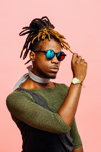 Portrait of a young man in green with dreadlocks and blue sunglasses, isolated on pink