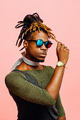 Portrait of a young man in green with dreadlocks and blue sunglasses
