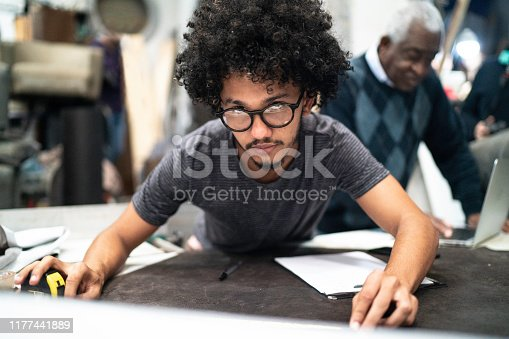 Portrait of a young man measuring a fabric in an upholstery workshop