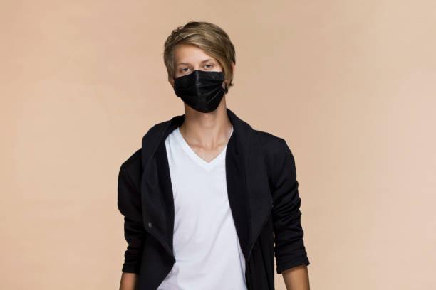 Porträt eines jungen Mannes auf einem Kaffee-Hintergrund mit einer Maske schützt vor dem Virus, schwarze Maske – Foto