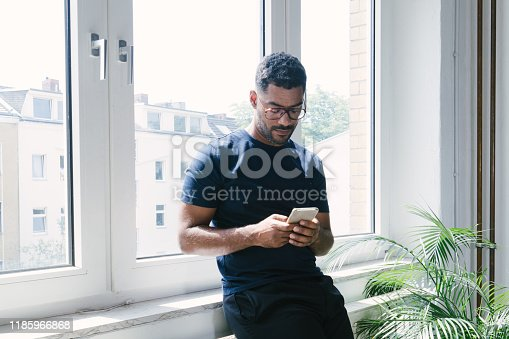 Portrait of a young man on the phone indoors