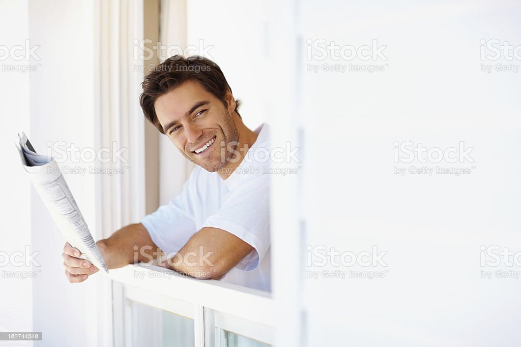 Portrait of a young man reading newspaper early morning royalty-free stock photo