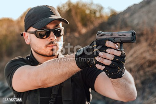 Portrait of a young man shooting a hand gun outdoors, close-up.