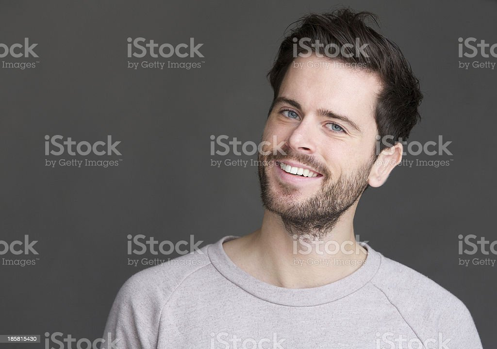 Portrait of a young man smiling on isolated gray background stock photo
